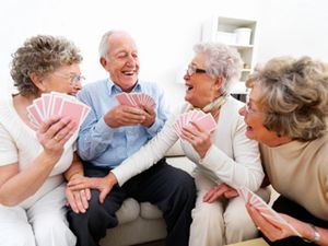 An elderly man has fun playing card game with three senior ladies.