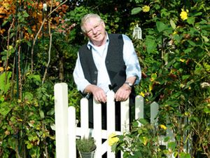 An elderly man stands smiling at a garden gate.