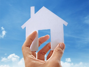 A hand is holding a scissors cut of a house with blue sky in the background.